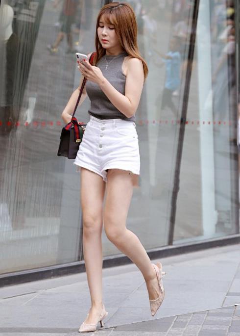 街拍:小姐姐一件白色单肩背心搭配低腰牛仔短裤,尽显时尚魅力插图