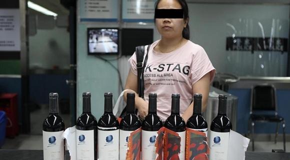 女子将高价酒伪装成廉价酒入境被当场识破